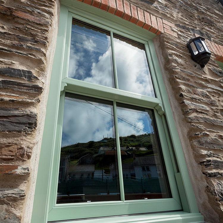 An exterior shot of a green sliding sash window